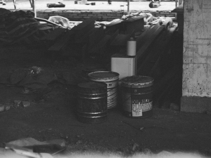 grayscale photo of cans on the floor