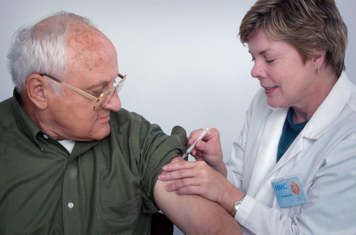 woman injecting syringe on mans arm