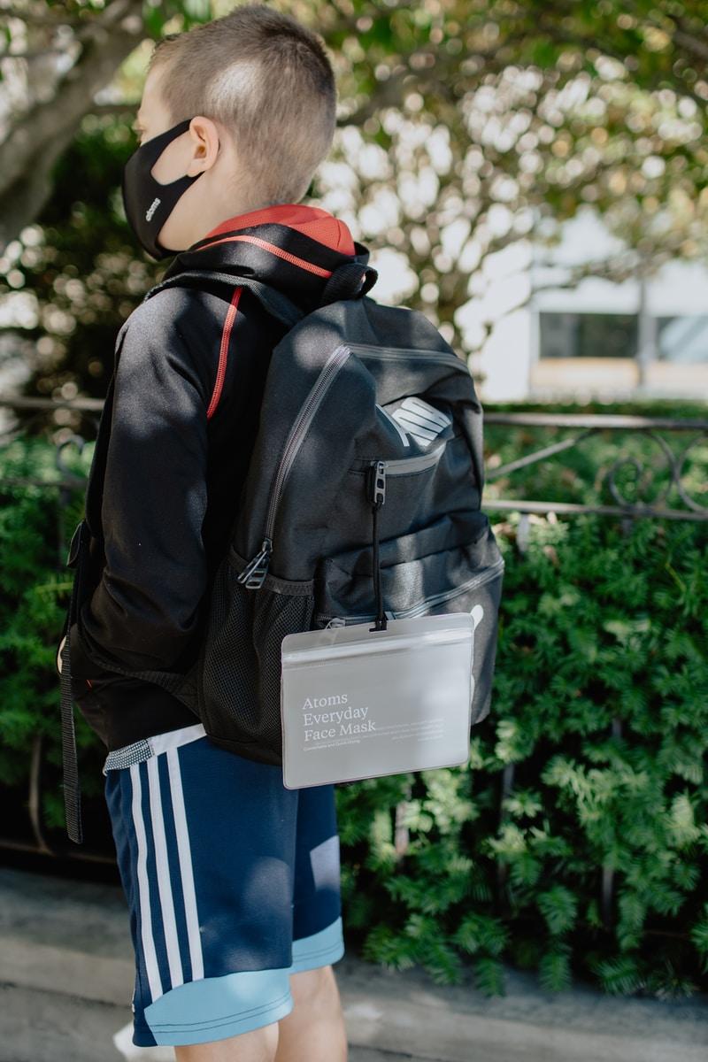 person in black leather jacket wearing white helmet